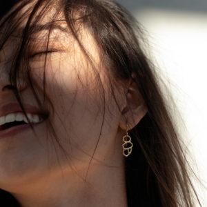 femme portant boucles d'oreilles or