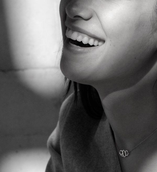 femme souriante portant collier